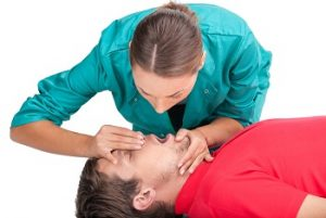 Image of woman performing mouth-to-mouth CPR